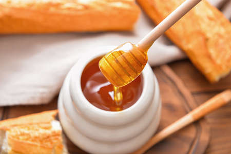 Sweet honey and bread on table
