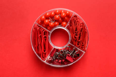 Box with clips and pins on color background