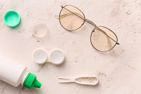 Contact lenses, glasses and solution on light background Stock Photo