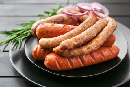 Plate with tasty grilled sausages on table Standard-Bild