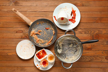 Dirty kitchenware and tableware on wooden background