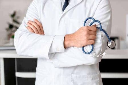 Male doctor near reception desk in clinic, closeup