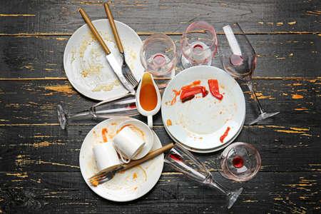 Dirty tableware on dark wooden background