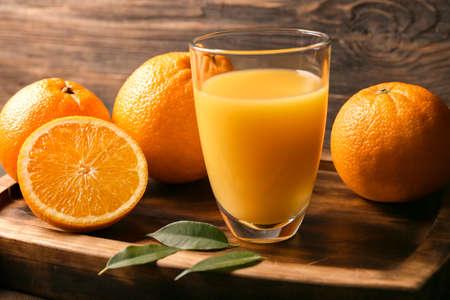 Glass of fresh orange juice on wooden background