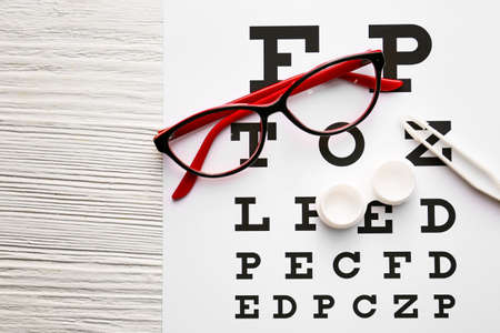 Contact lenses, glasses, tweezers and eye test chart on table