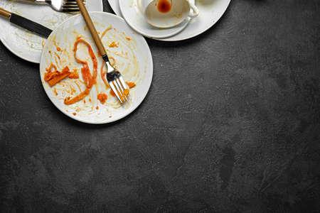 Dirty empty tableware on dark background