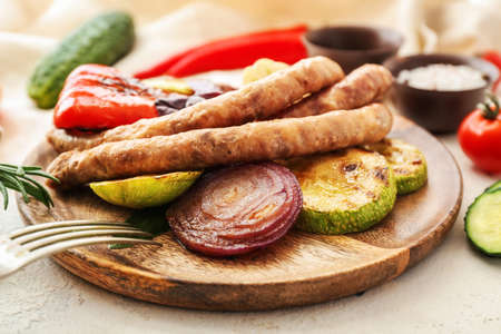 Plate with tasty grilled sausages and vegetables on table