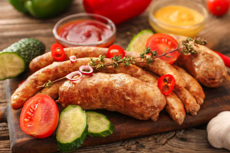 Board with tasty grilled sausages and vegetables on table