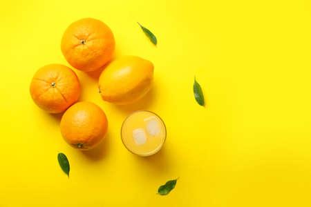 Glass of fresh orange juice and fruit on color background Standard-Bild