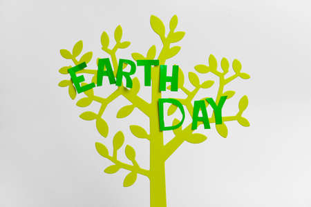 Figure of tree with text EARTH DAY on light background