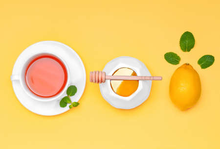 Tasty honey with lemon and cup of tea on color background Standard-Bild