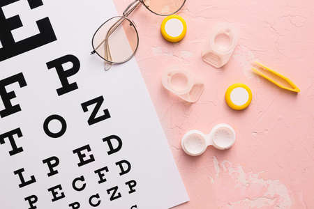 Contact lenses, glasses, tweezers and eye test chart on color background Standard-Bild