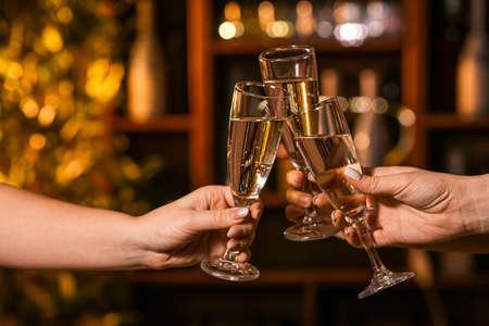 Women clinking glasses of tasty champagne in bar