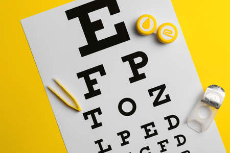 Containers with contact lenses, tweezers and eye test chart on color background Standard-Bild
