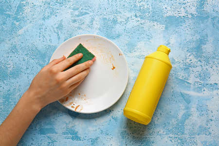 Woman washing dirty plate on color background Standard-Bild