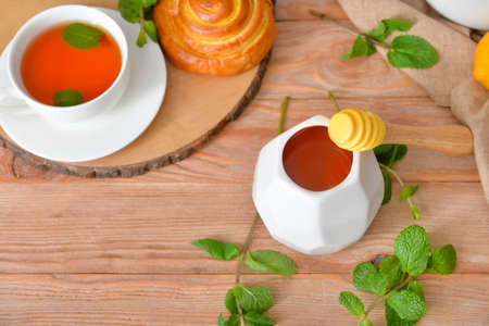 Tasty honey with bun and cup of tea on wooden table