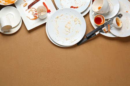 Dirty empty tableware on color background