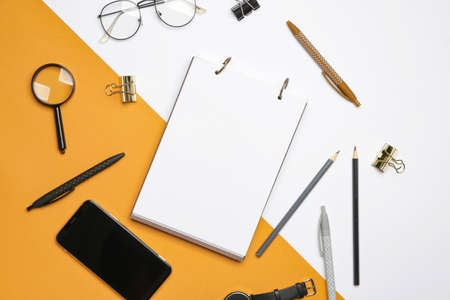 Notebook with school supplies and mobile phone on color background