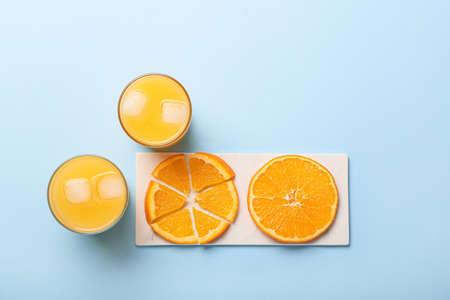 Glasses of fresh orange juice and fruit on color background