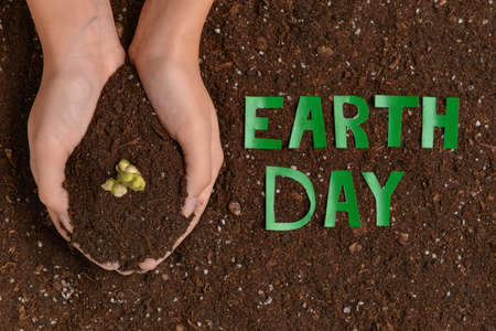 Female hands with soil and text EARTH DAY