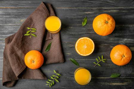 Glasses of fresh orange juice and fruit on wooden background
