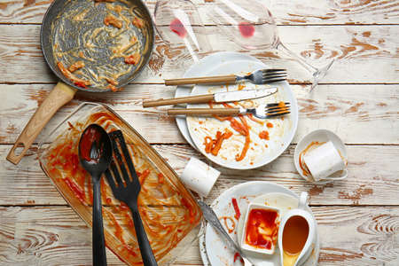 Dirty empty dishes and kitchenware on wooden background Standard-Bild