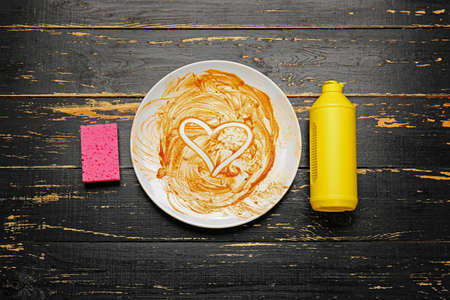 Dirty empty plate, detergent and sponge on dark wooden background