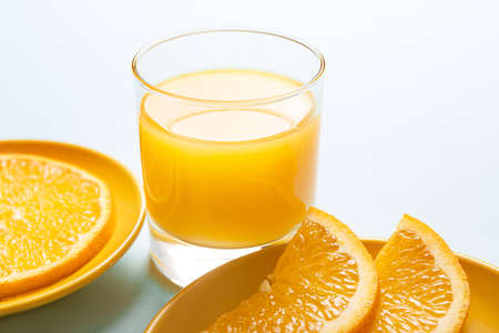 Glass of fresh orange juice and fruit on table