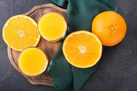 Glasses of fresh orange juice and fruit on dark background
