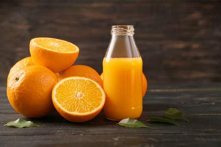 Bottle of fresh orange juice and fruit on wooden background Standard-Bild