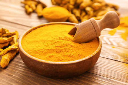 Bowl with aromatic turmeric on wooden background