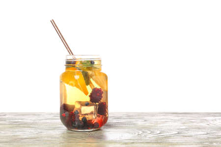 Mason jar of cold tea on table against white background Stock Photo