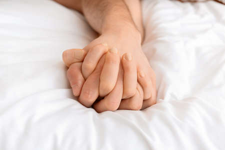 Hands of young couple sleeping in bed
