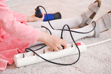Little girl playing with electric extension cord and blow dryer at home