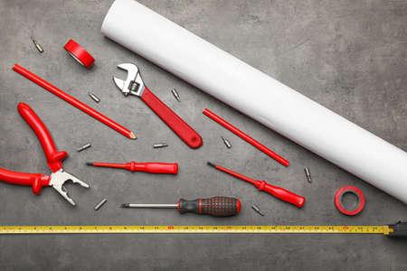 Builder's tools and blueprint on dark background Standard-Bild