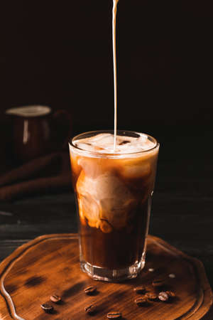 Pouring of milk into cold coffee in glass on table Stockfoto