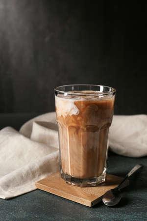 Glass of tasty iced coffee on dark background