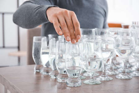 Young man playing music on glasses with water at home, closeup