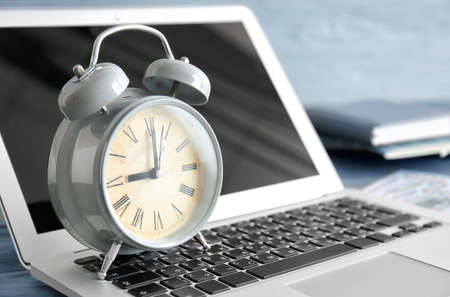 Alarm clock with laptop on table, closeup. Time management concept