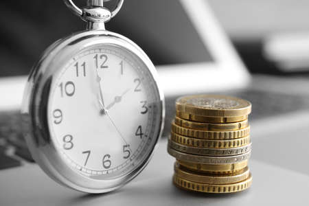 Coins and clock on laptop, closeup. Time management concept 免版税图像