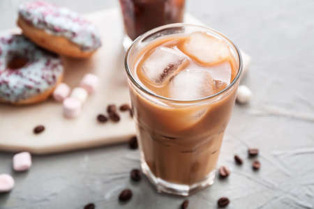 Glass of tasty iced coffee on gray background