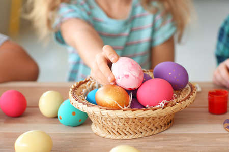 Little girl with painted Easter eggs at home