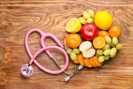 Plate with healthy products and stethoscope on wooden table