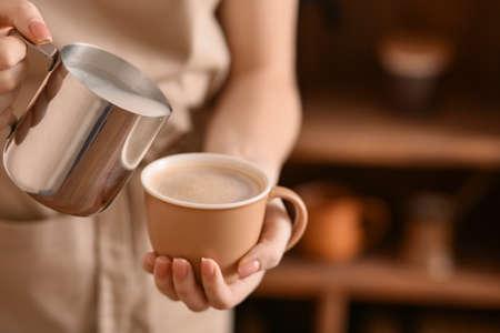 Barista preparing tasty cappuccino in cafe, closeup