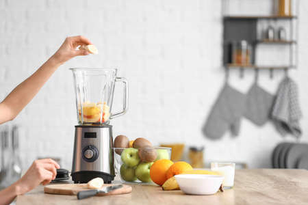 Young woman making fruit smoothie in kitchen at home Reklamní fotografie