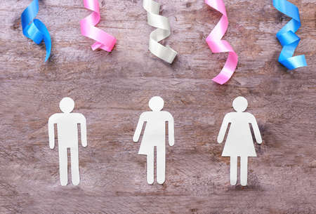 Human figures with ribbons on wooden background. Concept of
