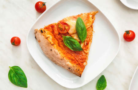 Plate with slice of delicious pizza Margherita on table