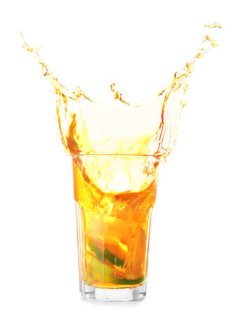 Glass of tasty cold ice tea with splash on white background Imagens