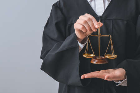 Female judge with scales of justice on light background, closeup