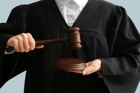 Female judge with gavel on light background, closeup Stock Photo